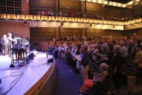 The audience at Garrison Keillor's Prairie Home Companion sing along. May 2, 2015. Photograph by Brian Yoder Schlabach. (https://www.goshen.edu/wp-content/uploads/sites/11/2015/05/15_APrairieHomeCompanion_031_bys-1366x911.jpg)