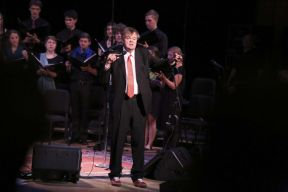 Garrison Keillor and the Goshen College Choir record A Prairie Home Companion May 2, 2015 Photograph by Brian Yoder Schlabach. (https://www.goshen.edu/wp-content/uploads/sites/11/2015/05/15_APrairieHomeCompanion_079_bys-1366x911.jpg)