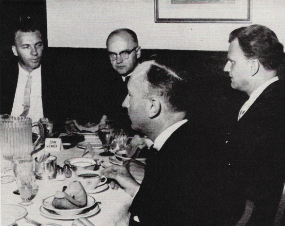 Black and white photo of four men sitting around a table with food on it.