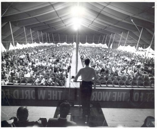 A man stands with his back facing the camera. He is preaching to a large crowd under a large white canvas tent.