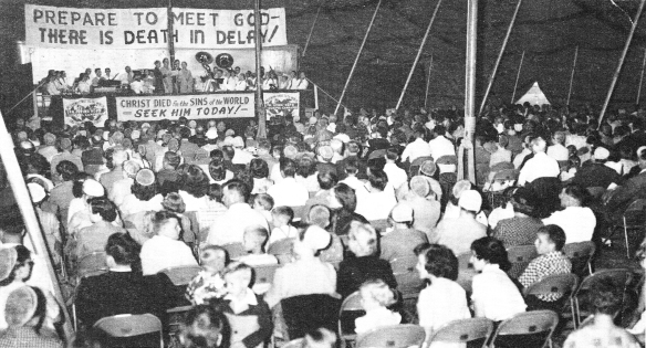 A large crowd of people sit under a large canvas tent watching a preacher behind a podium. Large signs are posted behind him, proclaiming Christian messages.