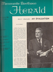 "A magazine cover. It is an emerald green color and features the words ""Mennonite Brethren Herald"" in white at the top of the page. In the middle of the page is a white box with text, featuring an image of Billy Graham speaking to an audience while holding an open Bible."